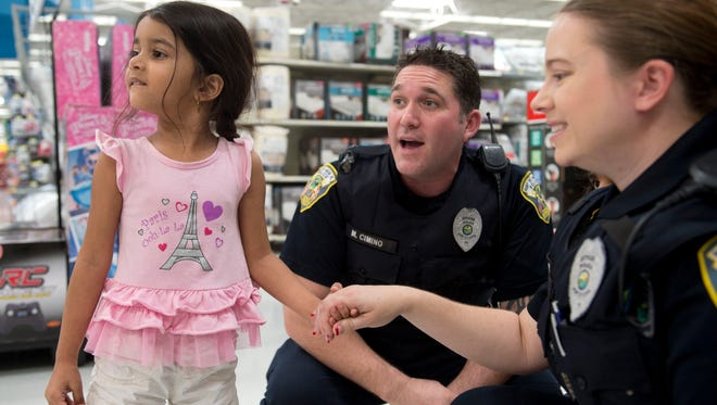 Jada Moore, 4, of Port St. Lucie, surveys the Wal-Mart toy department with Port St. Lucie Police Officers Michael Cimino (center) and Ariel Dennis during the department's annual Shop with a Cop event Dec. 14, 2016, at the Wal-Mart in Port St. Lucie.