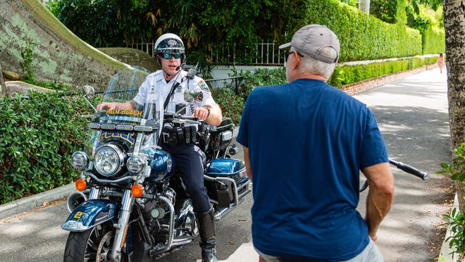A Palm Beach motorcycle officer stops a bicyclist from entering the Lake Trail due to new restrictions in Palm Beach on March 24.