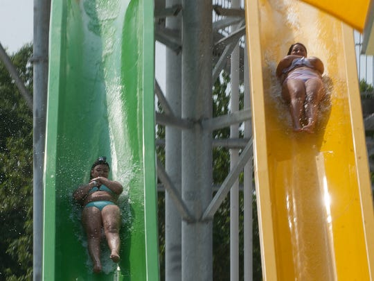 Tianna Mason, left, and Taylor Cheathan, right, slide down the giant water slide at Splashplex, a water park that is part of Funplex in Mount Laurel.