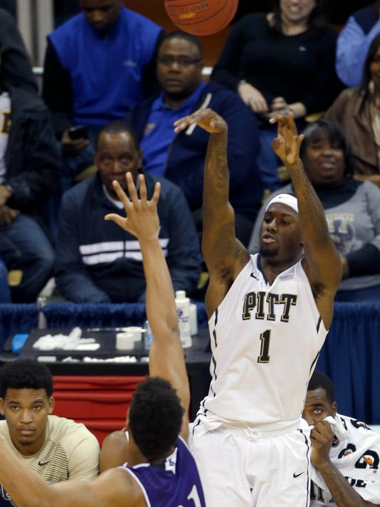 Pittsburgh's Jamel Artis (1) hits a 3-point shot over Holy Cross's Malachi Alexander (21) in the second half of an NCAA college basketball game, Tuesday, Dec. 23, 2014, in Pittsburgh. Pittsburgh won 58-39. (AP Photo/Keith Srakocic)