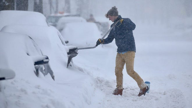 Gavin Smith tries to dig out his car on Park Avenue in Rochester.