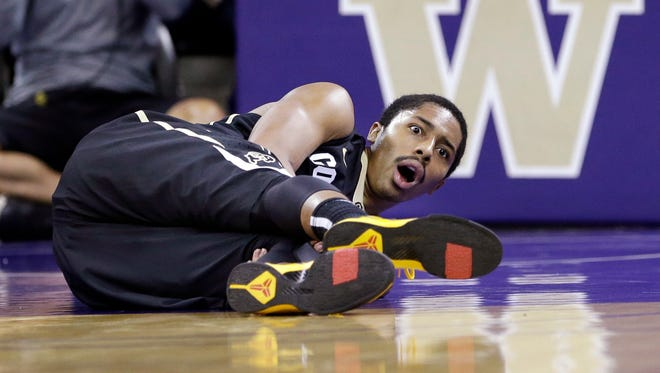 Colorado's Spencer Dinwiddie looks up after falling to the court against Washington with an injury in the first half of an NCAA college basketball game.