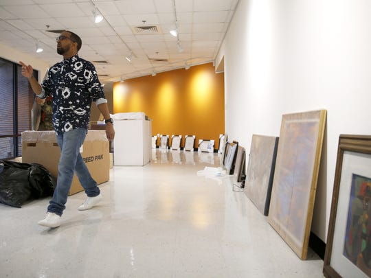 """Khalil Kinsey, son of Bernard and Shirley Kinsey, owners of the """"The Kinisey Collection"""" ,works to display the over 100 pieces of African-American history, artifacts, documents, and artwork at the Foster-Tanner Fine Arts Center on FAMU's campus Thursday."""