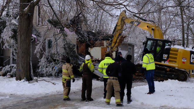 An excavator tears down a house destroyed in a fire in the 900 block of Johnson Avenue during the early morning hours of Wednesday, Jan. 17, 2017.
