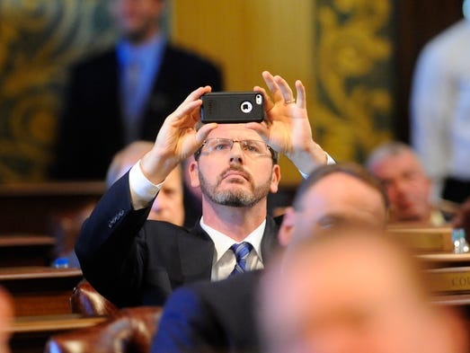 State Rep. Todd Courser takes a picture of the vote