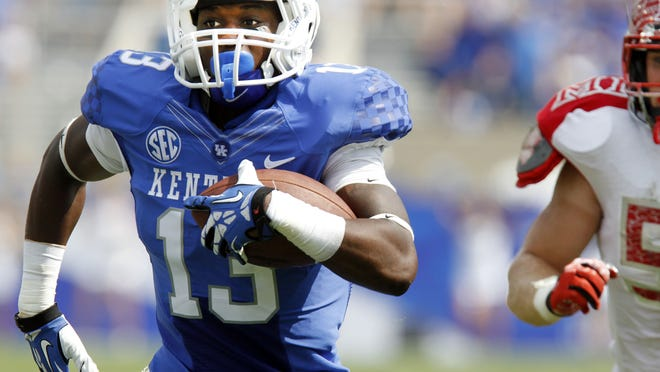 Kentucky's Jeff Badet runs past Miami of Ohio's Josh Dooley to score a touchdown in the fourth quarter of an NCAA college football game on Saturday, Sept. 7, 2013, in Lexington, Ky. Kentucky won 41-7. (AP Photo/James Crisp)