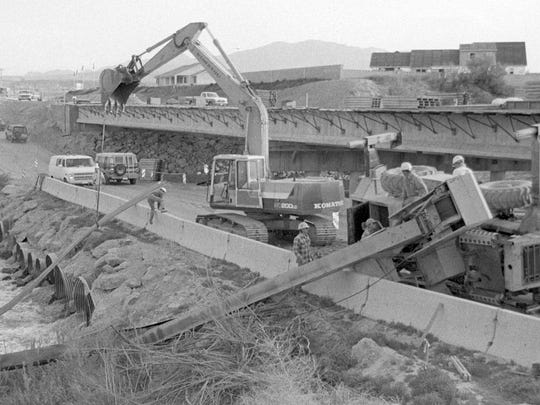 In April of 1992, Spectrum & Daily News photographer Loren Webb captured the then image after a crane tipped over during construction work on the bridge over the Virgin River on South River Road in St. George. A section of the old steel bridge that collapsed when the Quail Creek Dam failed in January of 1989 and necessitated the 1992 construction of the new River Road Bridge, can be seen in the now image taken by Spectrum & Daily News photographer Jud Burkett.