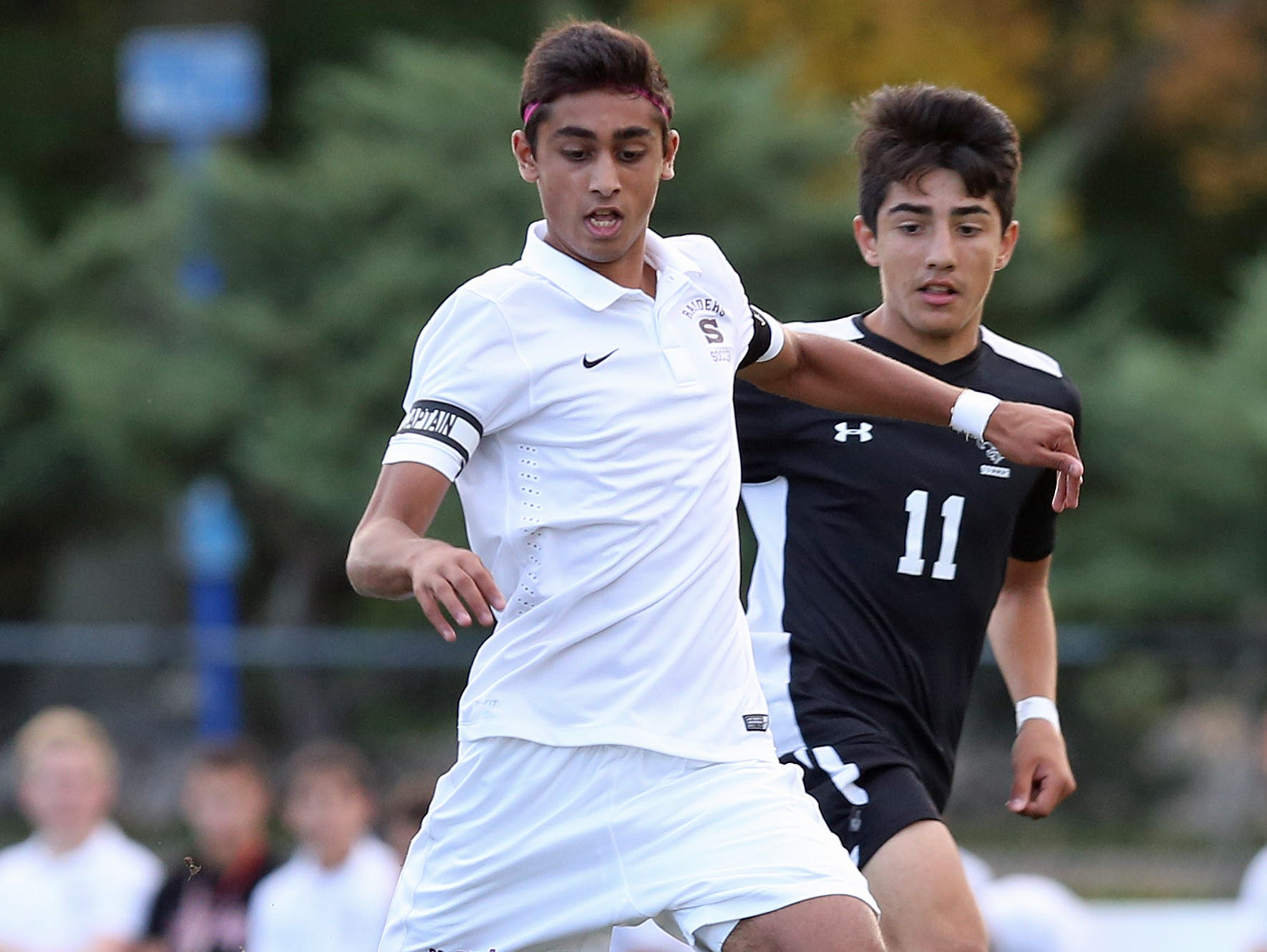Scarsdale's Fazel Shaikh (19) fires a shot for a first half goal in front of New Rochelle's Cristian Valencia (11) during a boys soccer game at Quaker Ridge School in Scrasdale Oct. 13, 2015. Scarsdale won the game 5-2.