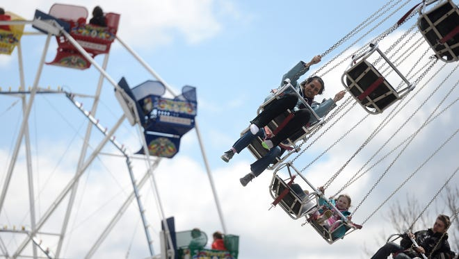 """I liked the way this one brought together multiple attractions at Bay Beach in one photo""  People ride the swings and ferris wheel at Bay Beach Amusement Park in Green Bay, Wis. on Saturday, May 3, 2014."