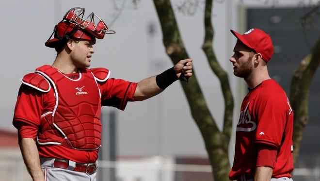 Reds catcher Devin Mesoraco talks with pitcher Tony Cingrani Thursday morning.