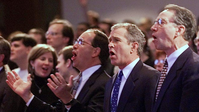 Republican presidential hopeful George W. Bush, center, sings with Sen. Charles Grassley, right, and Pastor John Palmer, left, during services at the First Assembly of God church on Jan. 23, 2000, in Des Moines.