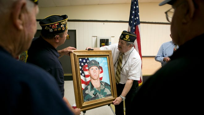 The Rome American Legion reveals an oil painting of Matthew Grimm, who died Jan. 2007 while serving in the U.S. Army in Iraq to his parents Jean and Eldon Grimm at the Rome Municipal Building, Tuesday, May 5, 2015.