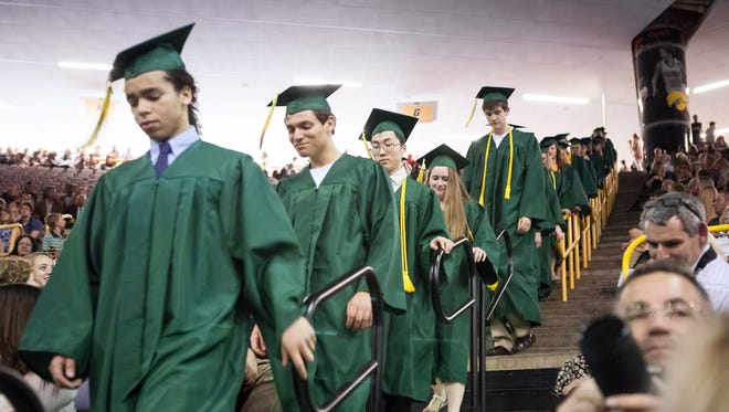 Members of the West High graduating class of 2015 walk down the stairs to the floor of Carver Hawkeye arena for commencement Saturday, May 23, 2015.