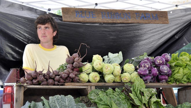 Pete Shriner, of Blue Ribbon Farm, helps customers with produce at the Asheville City Market on Charlotte Street Saturday. 6/14/14. Robert Bradley (rbradley@citizen-times.com)