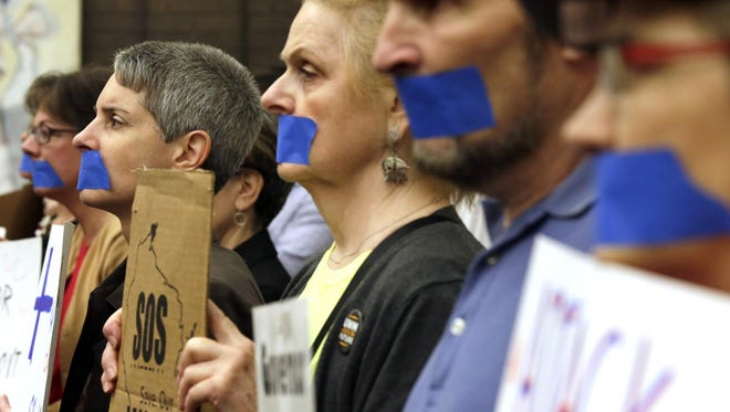 Protesters taped their mouths shut outside a Board of Regents meeting in Milwaukee in a demonstration against proposed changes to tenure in the University of Wisconsin System.
