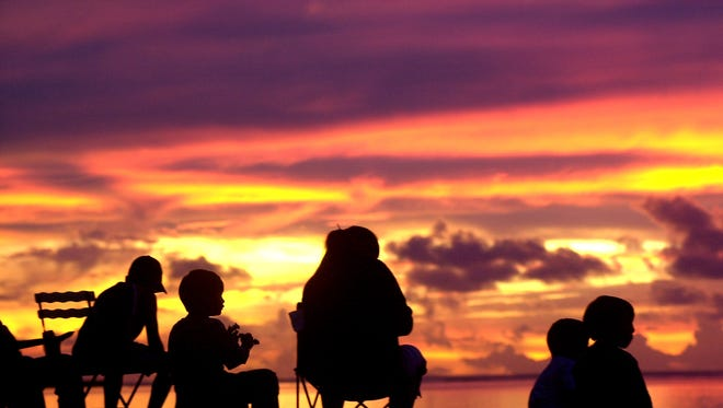 A family sit and relax as they watch the sun set along East Agana on Liberation Day in 2003.