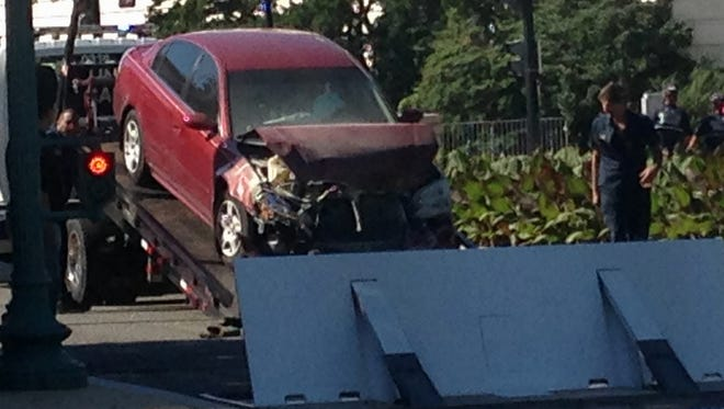 A car is is moved after crashing into a barrier on Capitol Hill in Washington on Friday, July 31, 2015.  Police say a person is in custody after a vehicle struck a barricade near the U.S. Capitol.