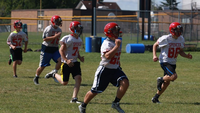 Spencer/Columbus players run towards the ball as they practice kick-off coverage, Aug. 10, on the practice field at Spencer High School.