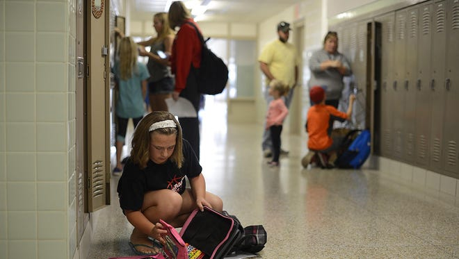 Olivia Shelly, 11, puts supplies in her locker during an open house and student orientation Wednesday at Pulaski Community Middle School. Shelly will be a sixth-grader this year.