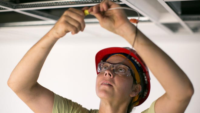 Electrician MaryJo Walker of Greece works on a job site at Mercy High School in Rochester earlier this month.