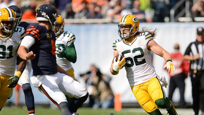 Green Bay Packers linebacker Clay Matthews (52) looks to elude Chicago Bears quarterback Jay Cutler (6) after Matthews made an interception in the fourth quarter during Sunday's game at Soldier Field in Chicago.