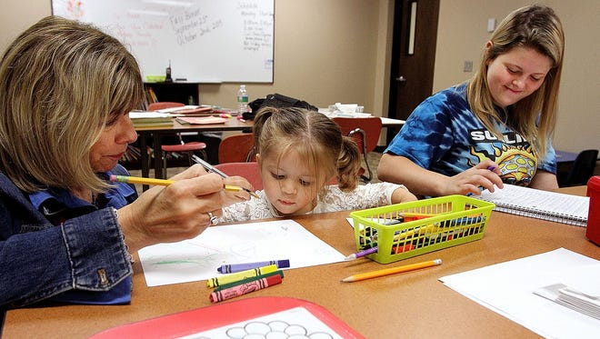 Melanie Casto (right), a Rushmore Academy senior, works on a Spanish language exercise while her daughter Elaina draws with Dianna Fry, a registered nurse and child watch aid in classroom dedicated to student parents and their children. Melanie is one of 15 young parents who utilize the schools new child watch service. James Miller/The Marion Star