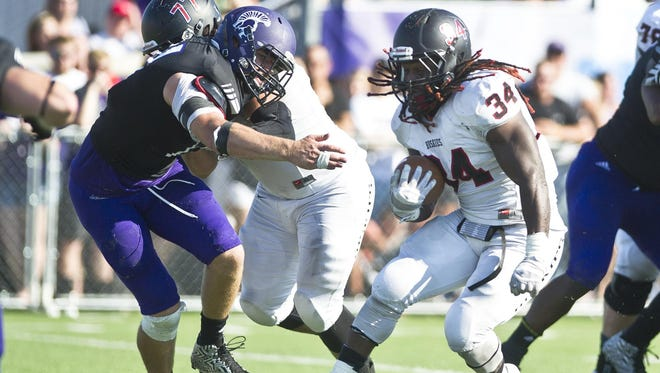 St. Cloud State running back Ledell White (34) rushes with the ball during Saturday's game at Winona State. St. Cloud State won the game 31-20.