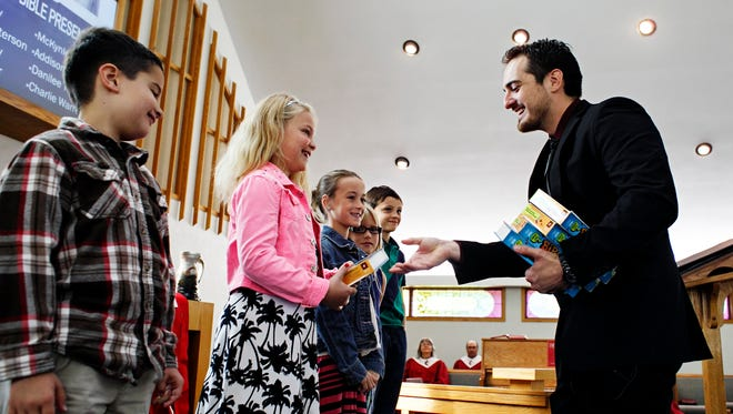 Pastor Tim Frasher hands out children's bibles during a service at Bloomfield United Methodist Church in Bloomfield on Sunday, September 13, 2015.