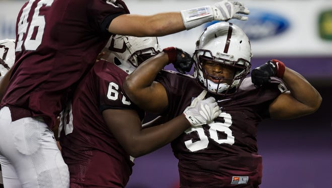 Dowling Catholic's Atlias Bell celebrates a sack during their semifinal game at the UNI dome on Friday, November 13, 2015 in Cedar Falls.