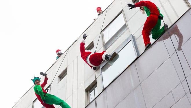 Following Ithaca tradition, Santa rappels onto  The Ithaca Commons each year.
