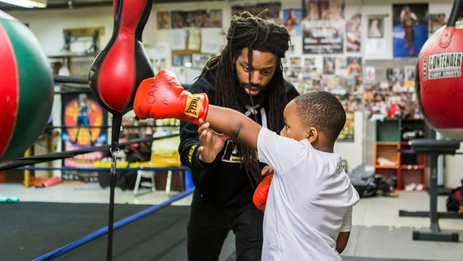 "Omar Douglas teaches proper boxing technique to six year-old Cameron Mackey in the upstairs gym at the William ""Hicks"" Anderson Community Center on Wednesday night, December 9, 2015."