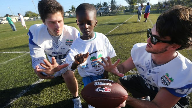 MTSU's football player Trevor Owens (43), left, and Jim Cardwell (38) teach M'ycahi Wilson, 6, how to throw a football during a youth football clinic Tuesday, Dec. 22, 2015, in connection with the Popeyes Bahamas Bowl.