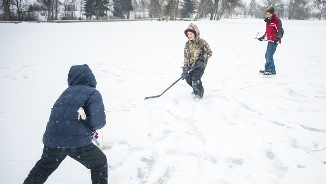 Left to right, Cole, Jack and Lane Gibney play hockey on Gibson Pond earlier this month.