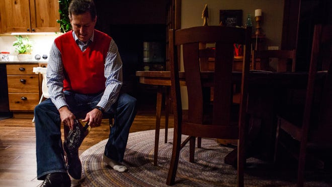 Republican presidential candidate Rick Santorum puts on his boots after spending the night at the home of friend and supporter Steve Boender in Oskaloosa at 6 a.m. Tuesday, Jan. 26, 2016.