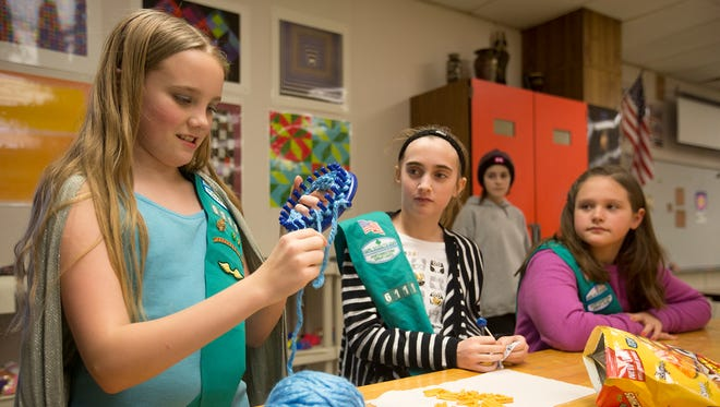 From left, Girl Scout Troop 6111 members Julia Caldwell, 10, shows off the scarf she is making for the  Evergreen Community Initiative to Ella Bancker, 11, center, Ellie Weisbrot, 10, at Plover-Whiting Elementary School, Tuesday, Jan. 26, 2015. The Evergreen Community Initiative gives scarves away to those in need. The scarves are currently hanging on trees by the Portage County Library.