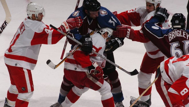 Detroit Red Wings and Colorado Avalanche players tangle in Denver on Feb. 5, 2004.