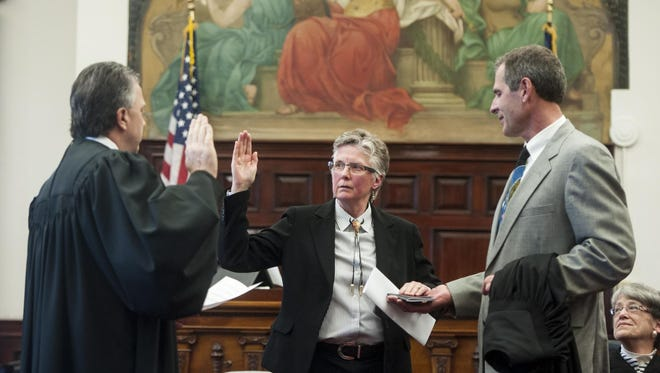 Elizabeth Best, center, takes an oath of office to become the newest 8th Judicial District judge from District Judge Dirk Sandefur, left, while her husband, Michael Best, holds the Bible in the Cascade County Courthouse on Monday.