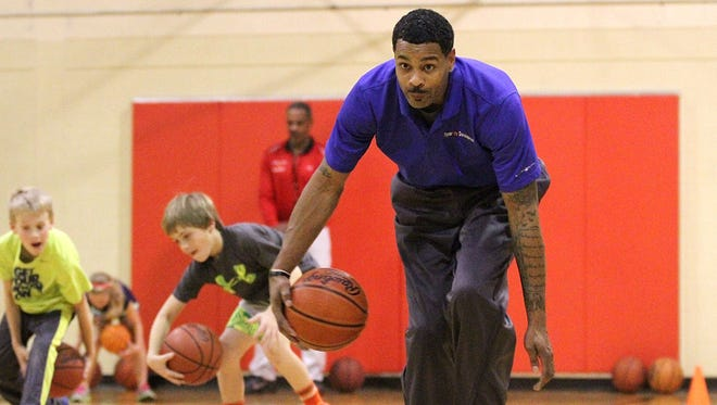 Ed McCants performs a pass-through-the-legs drill along with students participating in the McCants Reality Basketball class held at the gym at the Marion County Children Services campus two years ago. McCants was a standout at Marion Catholic, graduating in 2000.