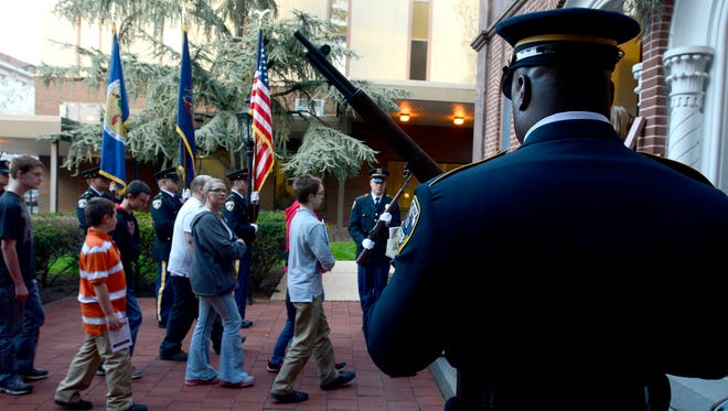 In this file photo from last year's 29th Annual Crime Victims' March & Candlelight Vigil, participants walk past the York City Police Honor Guard into Trinity United Church of Christ, Tuesday April 21, 2015. John A. Pavoncello - jpavoncello@yorkdispatch.com
