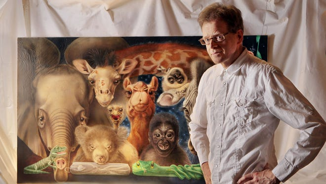 Lou Specker of White Oak stands with his original painting that was used for the Cincinnati Zoo poster in 1983.