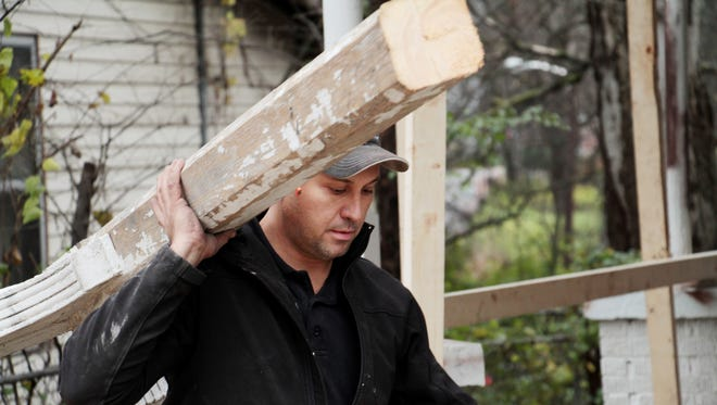 House flipper Troy Dean Shafer carries a salvaged 100-year-old porch column for a restoration at 1705 Nassau St. in Buena Vista near Nashville's Germantown neighborhood.