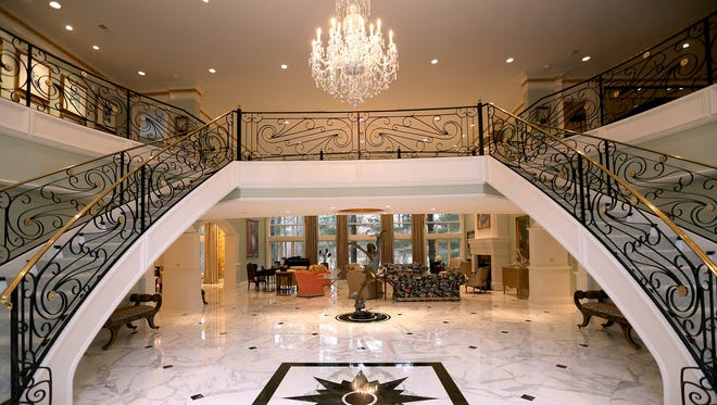 An Austrian crystal chandelier hangs over a double staircase with filigreed railings handmade by a Michigan metal artist in the foyer of a Farmington Hills, Mich., home once owned by a Detroit Public Schools vendor. The vendor, Norman Shy, is accused of cheating the school district out of millions of dollars with the help of 12 principals and an administrator.