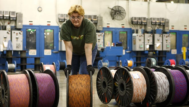 Wanda Cloran of Lawrenceburg rolls a large bobbin of telephone-line wire at General Cable?s manufacturing plant in Lawrenceburg, Ky.