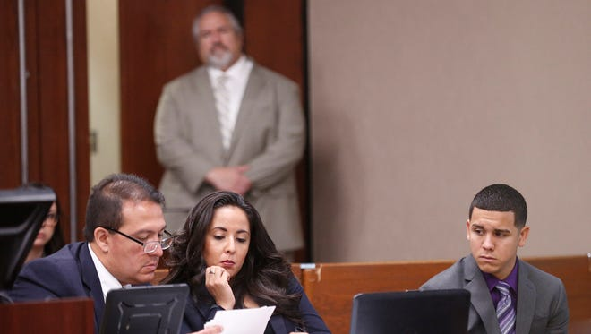Jan Michael Nieves Delgado, right, sits with his attorneys Thursday as they look at photos of the May 11, 2014, crash during the first day of his trial in the 168th District Court with Judge Marcos Lizarraga presiding. Delgado, a former Fort Bliss soldier, was arrested in the deaths of two construction workers who were working on the Spur 1966 bridge. Delgado is charged with two counts of intoxication manslaughter with a vehicle and two counts of manslaughter.