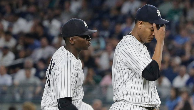 New York Yankees shortstop Didi Gregorius, left, talks to pitcher Ivan Nova as Nova waits to be relieved during the seventh inning of a baseball game against the Toronto Blue Jays, Wednesday, May 25, 2016, in New York.