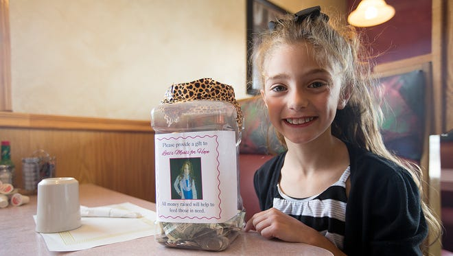 Alexis Ananiadis, 8, of Stevens Point sits at Olympia Family Restaurant with her jar accepting donations for her charity, Lexi's Love in Stevens Point, Friday, June 10, 2016.
