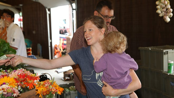 Stephanie Roberts, from the Shared Roots Farm in McGraw, helps a customer with daughter in hand Saturday at the Binghamton Farmers Market.