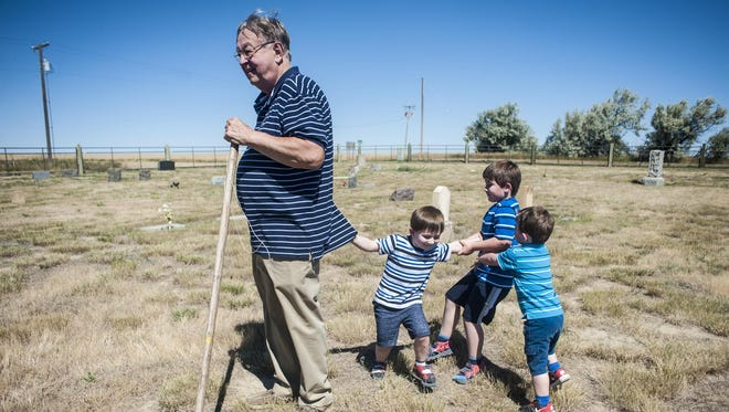 Dennis stands in Carter Cemetery while, Sammy, 3, Gabriel, 5, and Henry Nottingham, 2, play behind him Thursday. In mid-June, while the family was maintaining the cemetery, a rattlesnake rose up to attack Henry and his brother, Sammy, immediately pulled him away.