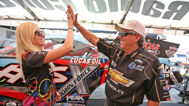 NHRA driver Courtney Force, left, high fives her driver dad John Force at Lucas Oil Raceway, Friday, September 4, 2015.