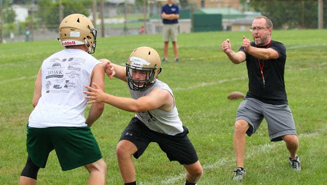 Vestal head coach Marty Fisher instructs some of his players during a drill on the opening day of practice.